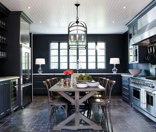 House_and_home_dark_black_kitchen_rustic_farmhouse_table_beadboard_ceiling_stainless_appliances_pavers_floor_marble_countertops